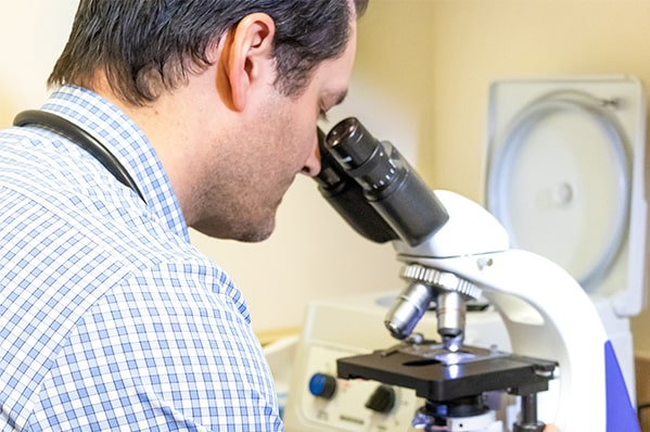 A man looking into a microscope